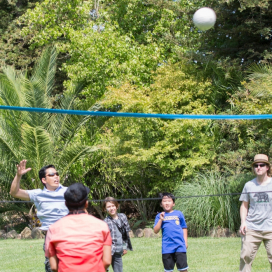 AV-ators and families play volleyball at the 2018 annual picnic